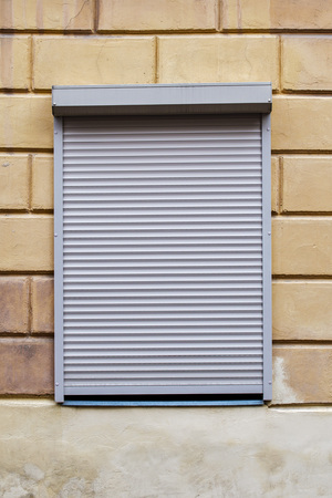 window with blinds on the brick wall Stock Photo