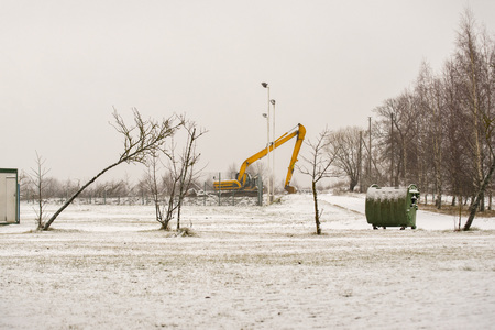 Big yellow excavator at construction site in winter.