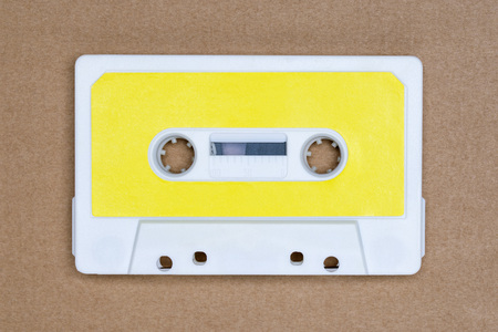 Retro white audio tape with yellow label on brown background Stock Photo