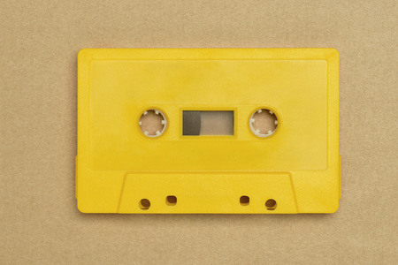 Retro yellow audio tape without label on brown background