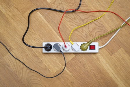 Colorful plugs attached into extension cord, phone, notebook chargers