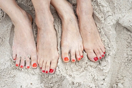 Feet of two women on a sand in the beach, red polished nails Stockfoto