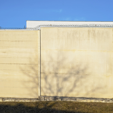 Building surrounded by big dirty wired wall. Tree shadow on a wall.