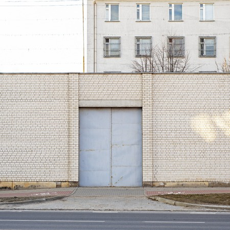 Entrance to abandoned building surrounded by big white brick wall. Industrial background. Banco de Imagens
