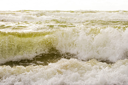 Wavy sea and cloudy sky in summer. Close-up view.