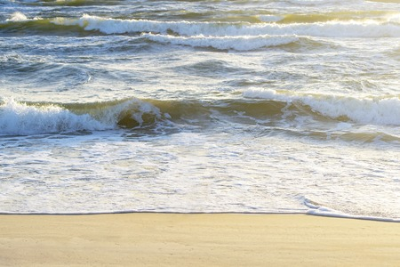 Wavy sea and sandy seashore in summer. View from top of dunes.