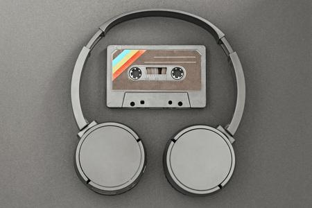 Retro audio tape and wireless headphones on black paper background. Banco de Imagens