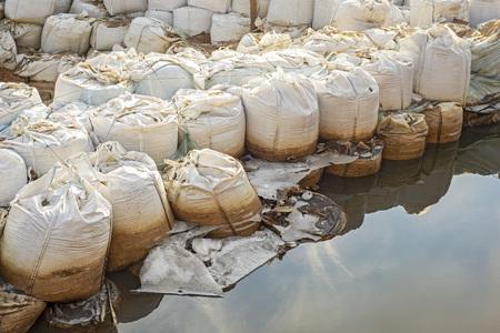 Lot of big white sandbags for flood defense. Banco de Imagens