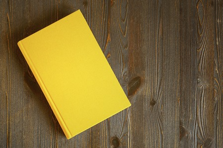 Yellow book on the wooden scratched table