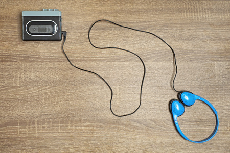 Retro walkman and blue headphones on the wooden brown background.