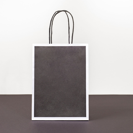 Blank black shopping bag standing on a dark paper surface.