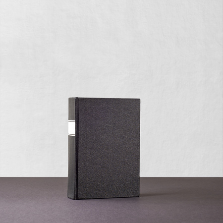 Black book with whiteframe on spine standing a dark paper surface near the white wall Banco de Imagens