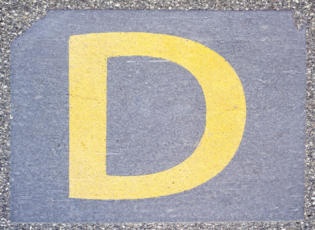 Letter D painted on the concrete pavement at the train station