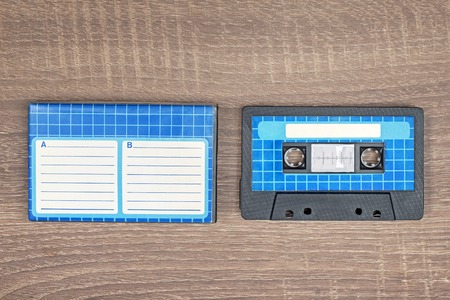Retro audio cassette and blue case with striped paper to write text. Brown wooden background.