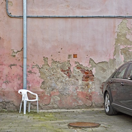Backyard of old weathered grunge house. Pink cracked brick wall, white chair and black car