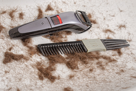 sink full of hair and dirty comb, trimmer