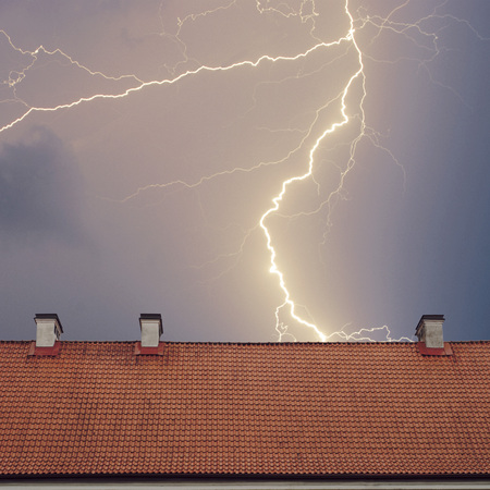 Thunderstorm with lightening over the roof at night