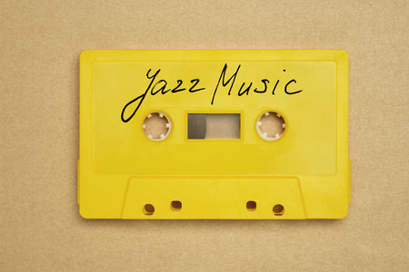 Retro yellow audio cassette tape with jazz music laying on the paper background