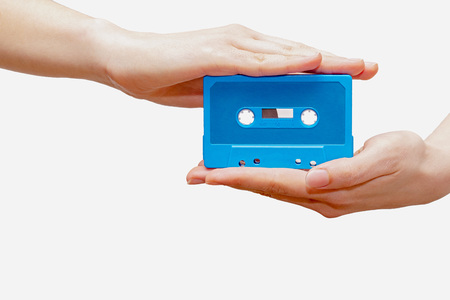 Hands holding blue cassette tape isolated in white background