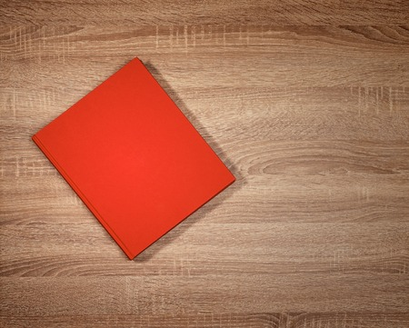 Red book on dark brown wooden table