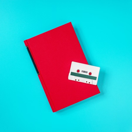 Retro white plastic audio cassette and red book laying on the green metal table