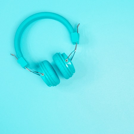 Pastel green headphone on pastel green metal table background
