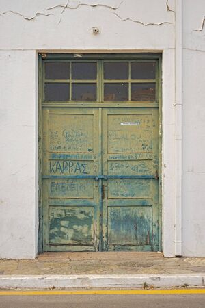 CRETE, GREECE - June 13, 2017: Abandoned house with wooden door. Dust words in greece written on dirty door. Editorial