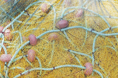 Yellow fishing net drying on the shore. Close up view