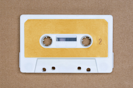 Retro white audio tape with yellow label on brown background. Side 2 Banco de Imagens