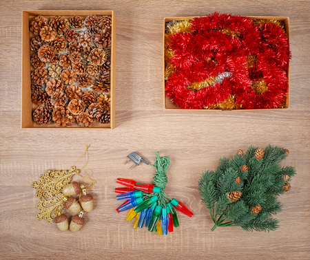 Traditional christmas tree decorations including baubles, fir cones, garland lights, glitter garland