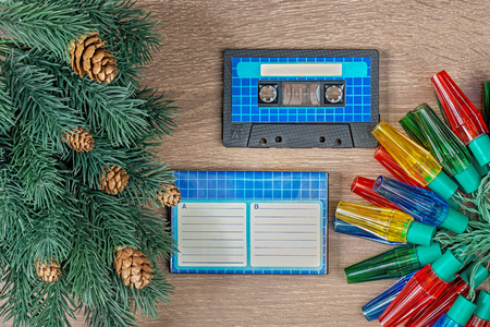 Retro blue audio cassette and christmas decorations on bown wooden background