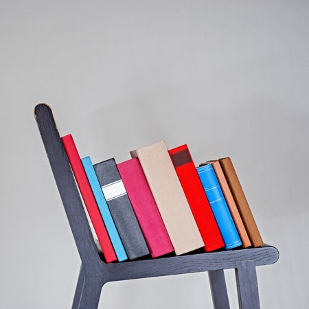 Colorful books on wooden chair near white stucco wall.
