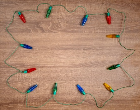 Christmas colorful lights on brown wooden background