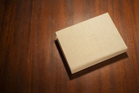 Beige color book on the wooden scratched table