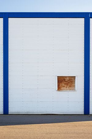 White Industrial warehouse wall in blue frame Standard-Bild