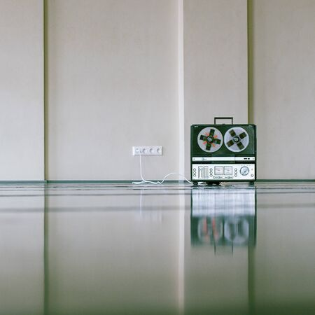 vintage analog magnet tape recorder standing on the floor near wall.