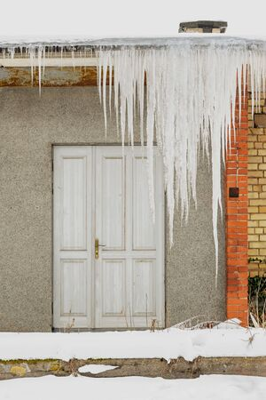 Huge icicles hang from the roof of an abandoned house with wooden door. Standard-Bild - 132486900