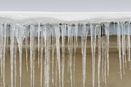 Big icicles hang from the roof of a house Standard-Bild - 132486901