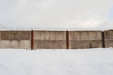 An area surrounded by dirty wired wall in winter. Standard-Bild - 132486912