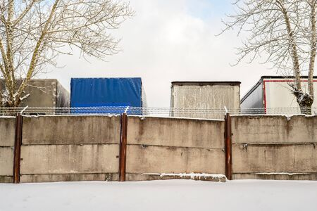 Trucks standing behind the fence wall in winter