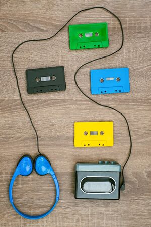 Vintage cassette player, colorful cassete and headphones on the wooden background Standard-Bild
