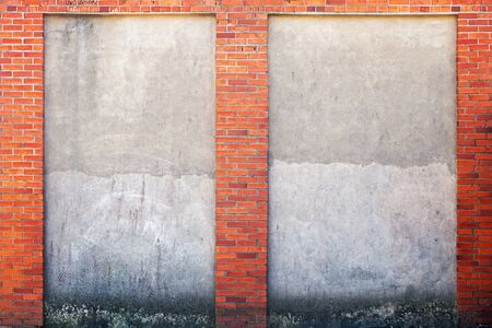 weathered stucco wall and red brick frame around. Standard-Bild