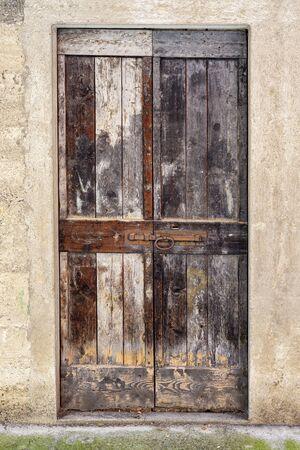Abandoned house, stucco wall with wooden door. Standard-Bild - 137639109
