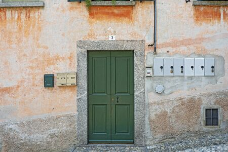 Old weathered grunge house. Green wooden door. Standard-Bild - 137723596