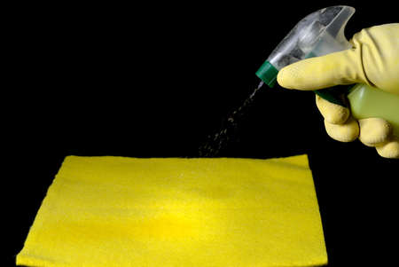 gloved hand throwing disinfectant liquid onto a yellow cleaning cloth