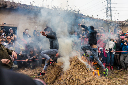 lunar month: Chinese Men Jumping a block of Fire and Straw for lunar month  festival