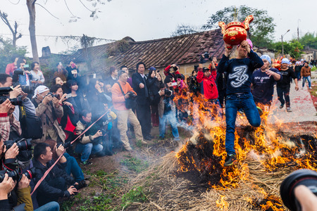 china people: Chinese Men Jumping a block of Fire and Straw for lunar month  festival