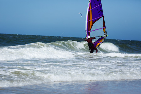 struggles: Unknown Windsurfer struggles with Sylt Waves Germany Stock Photo