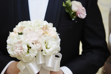 vows: Groom holding wedding bouquet