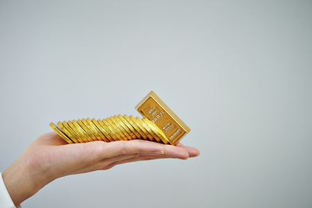 richness: Coins and gold bar on hand
